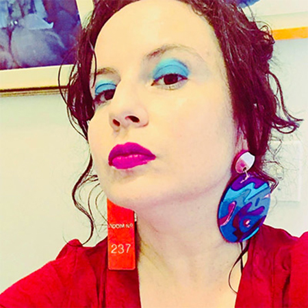 stylized photo of woman with blue eye shadow and big earrings looking down at camera