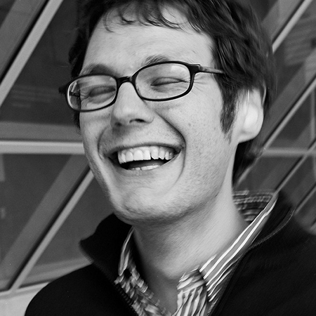 black and white photo of a young man wearing glasses and laughing