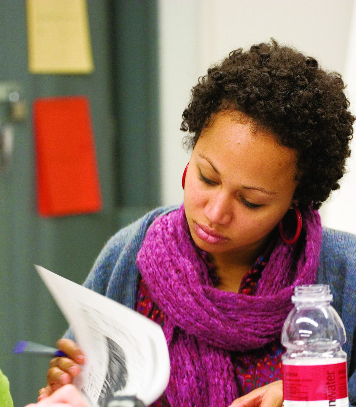 student wearing scarf reading a paper