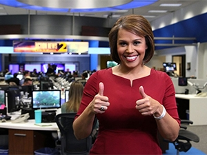 Jovita in the newsroom giving a thumbs-up to the camera