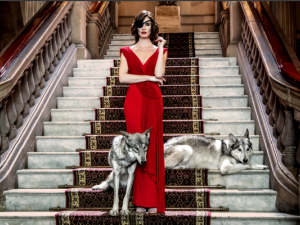 woman in fancy red dress on fancy grand staircase with wolves