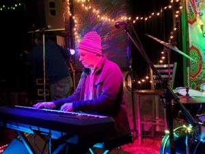 Man with striped hat playing a keyboard piano under purple light