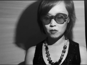 black and white photo of woman with sunglasses and a bead necklace