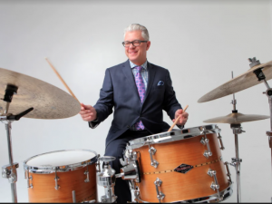 man in a suit playing a drum kit