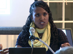 Woman with braids and a yellow scarf lecturing at a microphone