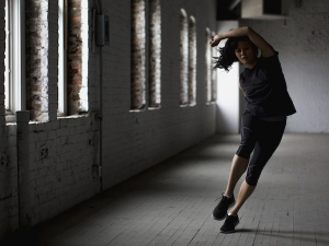 dancer, body twisted mid-move in an empty industrial space