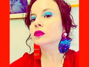 Dorothea Lasky wearing cool funky earrings and red blazer