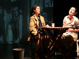 Two women on stage sitting across a table from each other (still from the production)