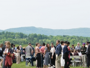 students and families on a lawn at commencement with mountains in the background