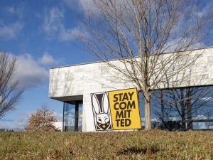 CAPA building with a yellow stay committed sign in the dead grass in front