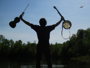 A man (seen from behind) stands with his feet in a lake on a sunny day holding two music instruments