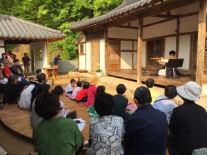 A musician plays the flute on the open air porch of the traditional Korean house in front of a seated audience