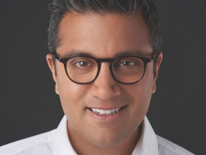 Asad Ayaz white shirt and glasses with a dark background