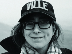 Audrey Shulman: woman wearing scarf, coat, glasses and hat that says Ville smiles at camera