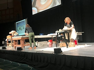 Artist making pottery onstage