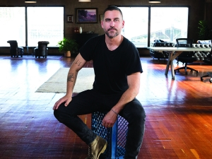 Bryn Mooser: A man sits on a chair in a room with a wooden floor wearing a black tee shirt and looking directly at camera