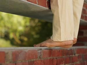 Close-up of dancer's bare feet on brick wall