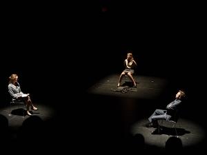 Three actors seated on stage