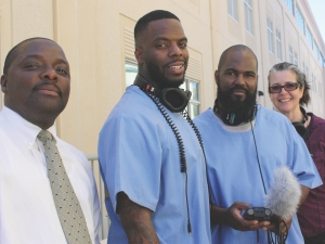 three men pose for the camera, two wearing blue, one with headphones, and one in white