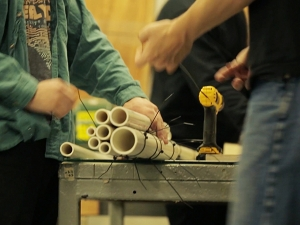 Students building an instrument out of PVC tubing