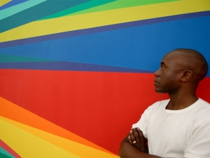 Odili Donald Odita in front of his own colourful painting