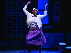 Woman dancing with joy on stage wearing a white sweater and purple skirt, blue lighting