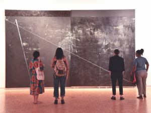 Museum goers observing a piece by Torkwase Dyson