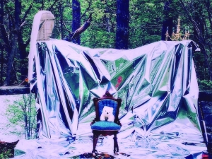 a forest draped in a white sheet with a chair at the center