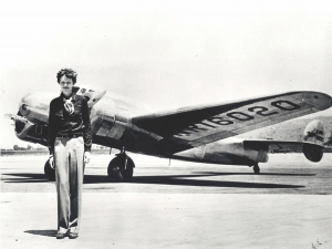 Amelia Earhart stands in front of her plane