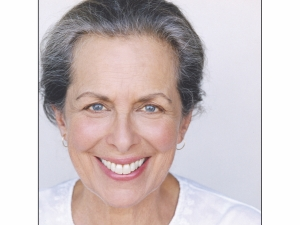 a woman with greying hair and white top smiles widely at the camera