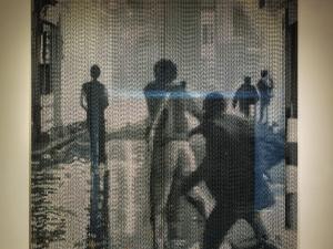 An art piece depicting a group of men, seen from behind, run down a street