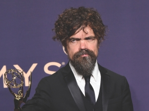 man with brown hair and beard holds emmy on the red carpet, purple background