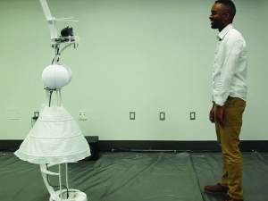 a man stands across from a robot wearing a white skirt, and smiles at it