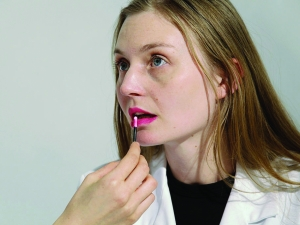 Close up of a woman's face while someone else applies lip gloss to her lips