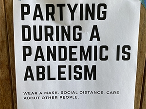 Image of sign partying during a pandemic is ableism