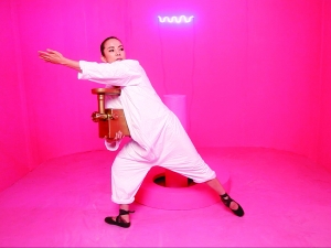 Jen Liu, wearing white, poses with arm extended in a bright pink/magenta painted room