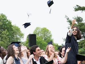 Photo of students throwing caps at graduation