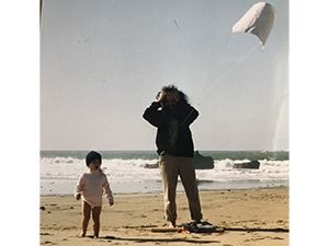 Image of young girl and man flying a kite on the beach