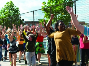 a group of dancers perform outside, they are raising their arms and wearing bright colors