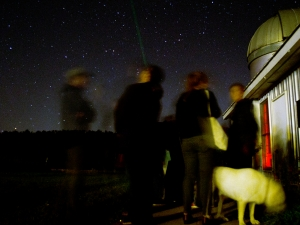 Students observing night sky outside observatory