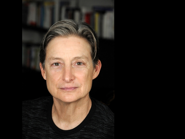 Woman with short grey hair and black shirt stares directly at camera