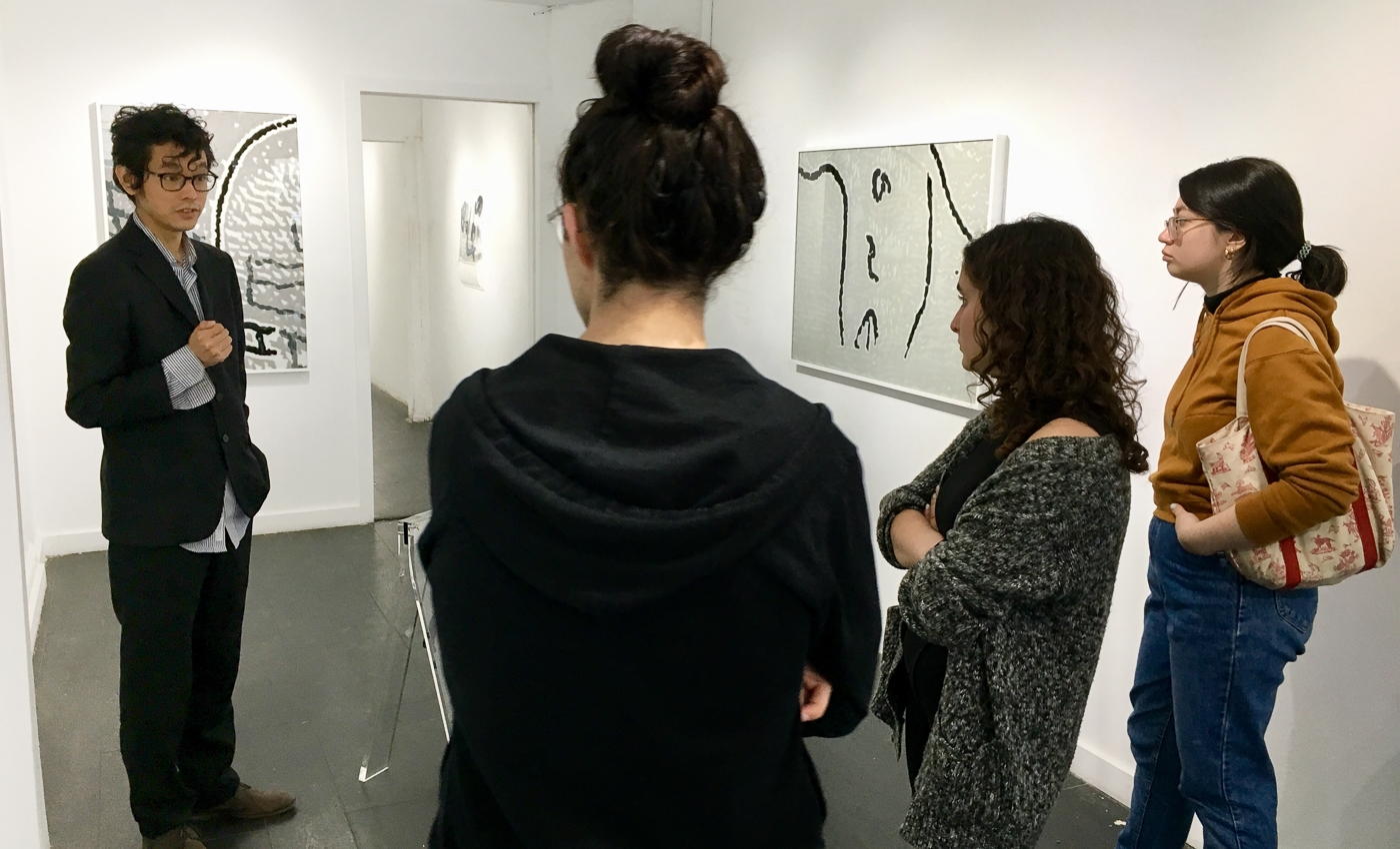 students speaking with gallerist at exhibition