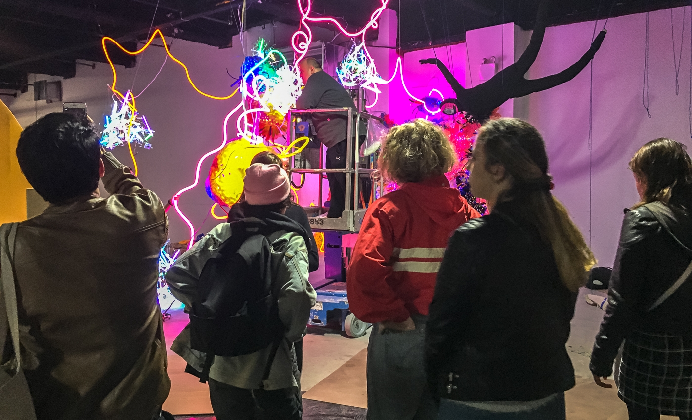 students looking at light art
