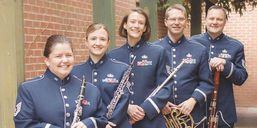the heritage winds group in blue uniforms with their instruments