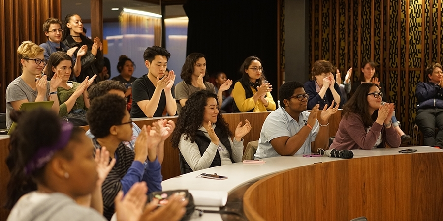 Group of students sitting in a tiered ring clapping