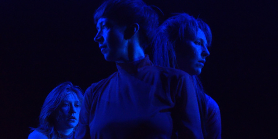 three women stand, looking in different directions, bathed in blue light