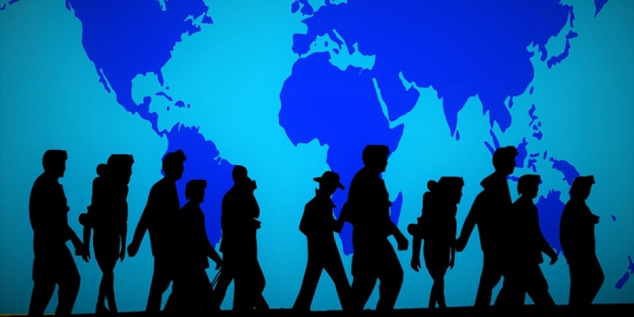 Black figures walking in front of a blue wall featuring the map of the world