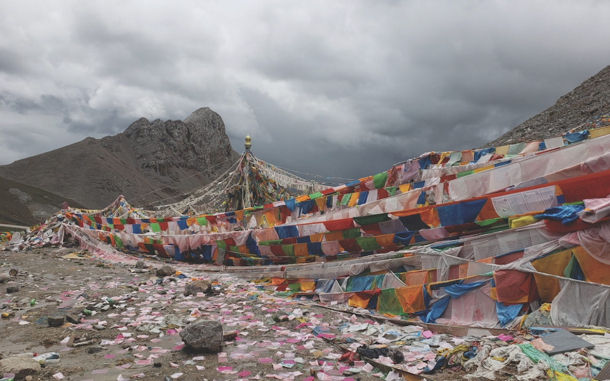 Many strings of colorful Tibetan prayer flags against grey mountains of rural Tibet