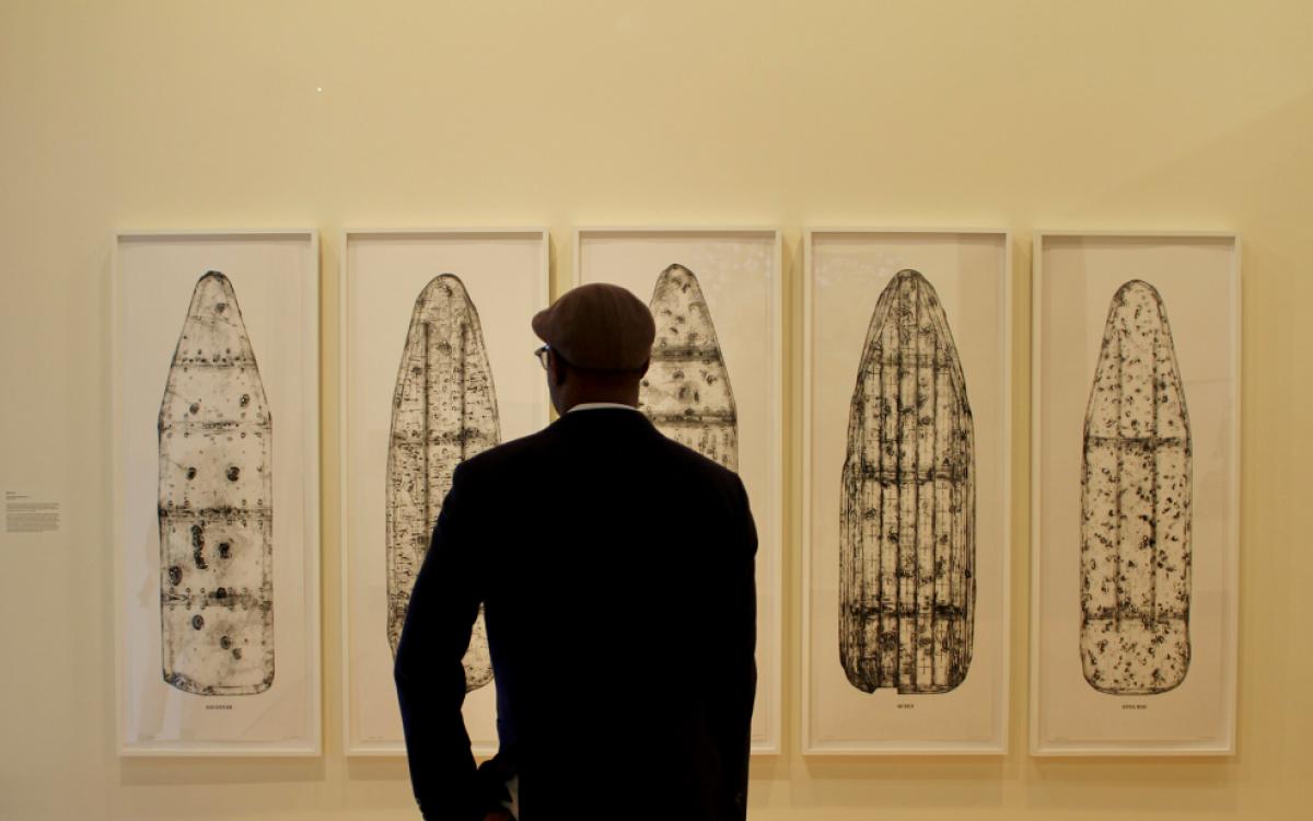 man looking at art