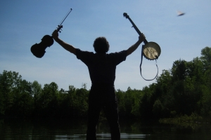 silhouette of man holding fiddle and banjo at dusk
